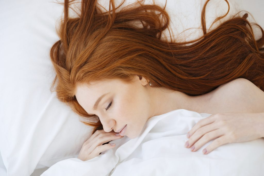 Tender cute young woman with long red hair lying and sleeping in bed