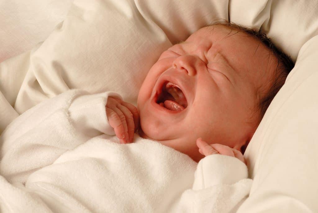 A tiny new born child crying sadly